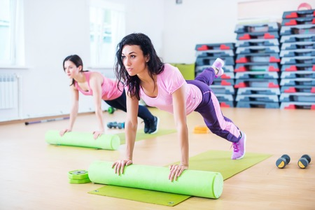 Fit woman stretching on floor using foam roller doing plank exercise.