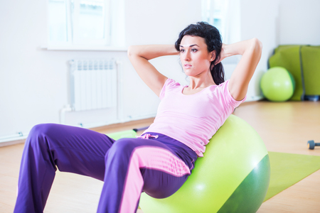 laying abs exercise: Fit women doing sit-ups on exercise balls.