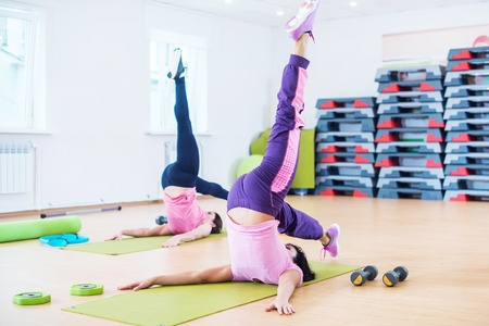 Fit young women stretching body in the fitness studio.