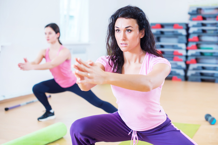 Fit women doing side lunges, exercises for legs, hips and buttocks. Stock Photo