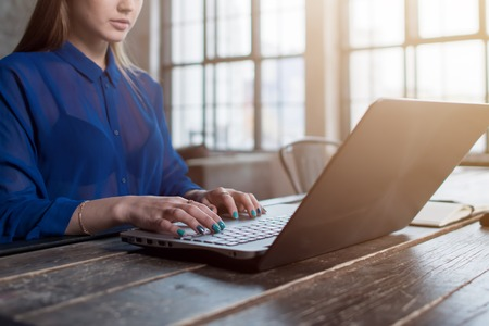 Cropped image of young female employee working on project typing text on laptop indoors