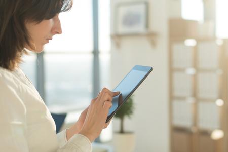 女性両手でタブレット pc と入力し、タッチ スクリーンとの wi-fi を使用してインターネット