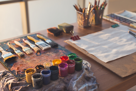 Painter workplace. Palette with brushstrokes and paintbrushes. Colorful gouache, crayons sets