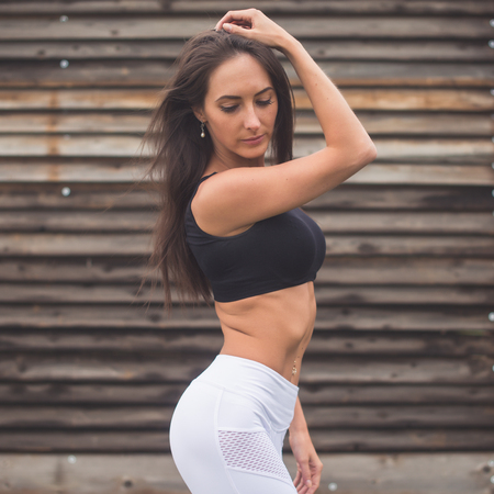 Young fit woman standing near wall outdoors portrait