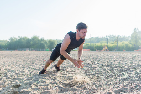 pushup: Fit man doing clapping push-ups during training exercise workout on beach in summer.