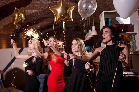 Happy pretty young women holding firework sparklers, balloons, glasses of wine celebrating a holiday in restaurant with Gothic interior Stok Fotoğraf