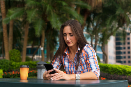 Young woman sitting outdoors reading and typing messages on her smartphone. Banco de Imagens