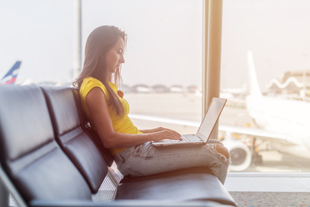 Young woman working on laptop sitting in a departure lounge of airport Stock Photo