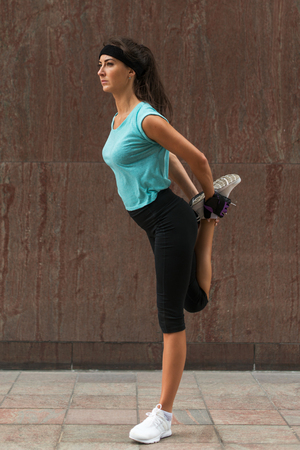 Young fitness woman doing warm-up exercise before running stretching her leg by performing knee to chest stretch on the city street. Sporty athlete preparing legs for cardio workout outdoors