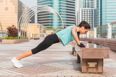 발을 피트 니스 여자 상승 된 팔 굽혀 펴기 도시의 벤치에. 실외 운동을하는 스포티 한 소녀 스톡 콘텐츠