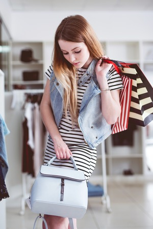 Young female shopper with shopping bags choosing the handbag matching her casual style Stock Photo