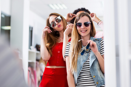 Young female friends trying on sunglasses laughing and having fun in accessory shop