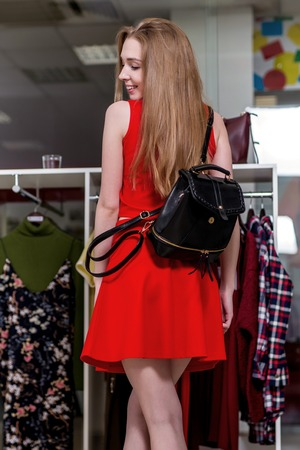 Full-length portrait of female model wearing red dress with long fair hair looking back showing new black leather backpack standing in shopping mall