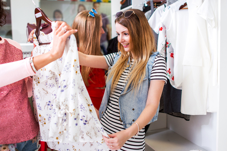 Pretty girl looking excited holding blouse offered by shopping assistant in clothing store Stock Photo