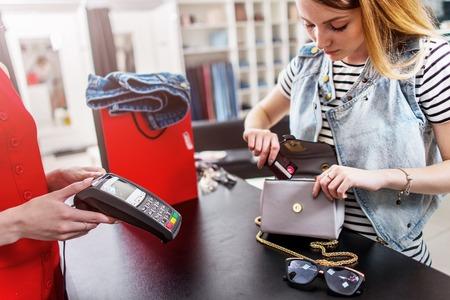 Giovane cliente femminile in piedi in cassa paga con carta di credito in negozio di abbigliamento Archivio Fotografico - 81363108