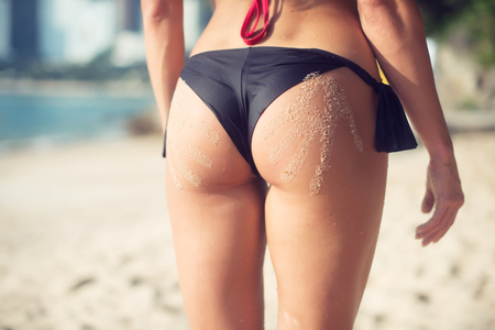 Close-up view of female buttocks in swim panties with two sand hand prints. Fit young woman standing on beach bright sunshine.