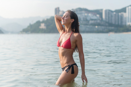 Slim young woman wearing bikini standing in sea with her eyes closed taking deep breaths enjoying fresh air, warm weather and bright sunshine in resort city