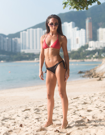 Full-length portrait of confident fitness female model wearing swimsuit standing on sandy beach with high buildings in background