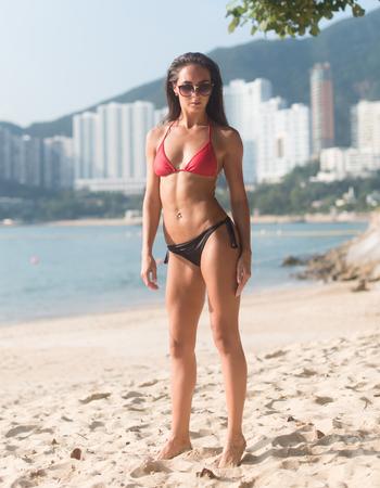 In voller Länge Porträt von zuversichtlich Fitness weiblichen Modell tragen Badeanzug stand auf Sandstrand mit hohen Gebäuden im Hintergrund Standard-Bild