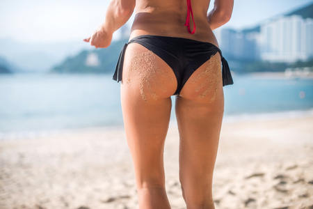 sinlight: Close-up view of female buttocks in swim panties with two sand hand prints. Fit young woman standing on beach bright sunshine.