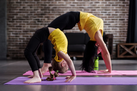 Two flexible girls of different age doing upward facing bow yoga pose working out Stock Photo