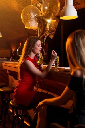 Porträt des Geburtstagsmädchens sitzend mit einem Glas Cocktail am Barzähler