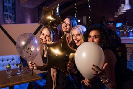 Vier mooie jonge Kaukasische vrouwen die ballons houden die nacht uit samen in trendy bar hebben
