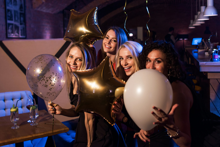 Vier schöne junge kaukasische Frauen , die Ballone halten , die zusammen in der modischen Stange zu machen Standard-Bild - 82157454
