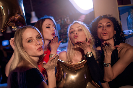 Group of attractive gorgeous girls blowing kisses looking at camera in nightclub Фото со стока