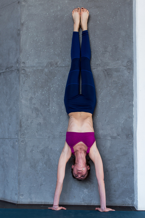 Skinny barefoot woman in sportswear doing handstand against the wall indoors
