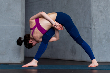 revolved: Sporty Caucasian woman practicing standing side angle twist position during yoga class