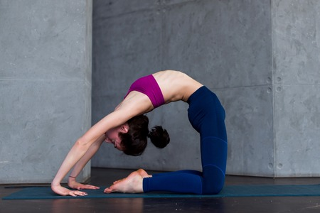 Skinny flexible female yogini bending backwards doing stretching exercises on floor in a room