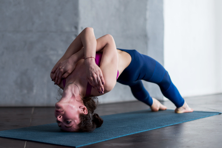 Young Caucasian female doing challenging headstand backbend yoga pose with her arms crossed on chest Stock Photo