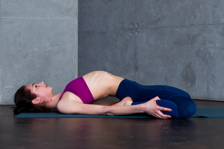 Slim young woman lying in Supta Virasana, reclining Hero Pose, stretching abdominal and back muscles on mat in gym