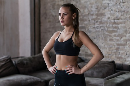 Fit sexy female model in black sportswear with pony tail posing in loft interior looking away from camera Stock Photo