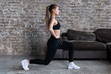 Profile view of sporty girl doing lunges working-out leg muscles and glutes in loft interior