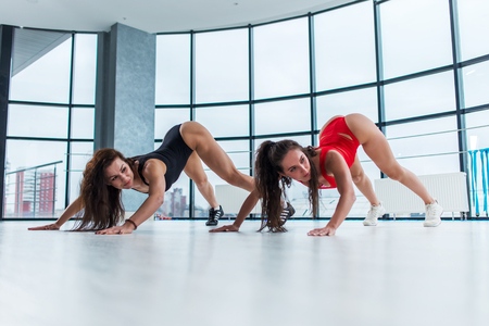 Sporty young women attending gymnastics classes. Female athletes stretching back and legs standing on tiptoe and crawling forward arching back in studio Stock Photo