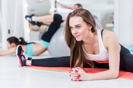 Cute smiling young lady in sportswear doing advanced middle split exercise bending over leaning on arms in gym