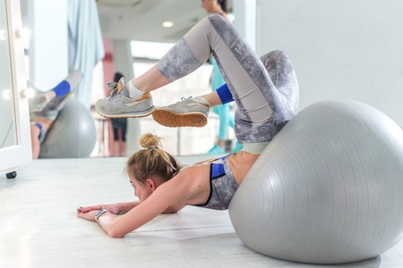 Fit young woman doing stretching exercise for back on fitness ball lying trying to reach head with feet in sports club Stock Photo