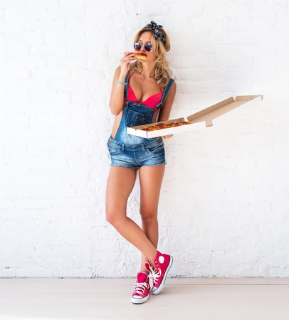 Young sexy woman eating a piece of pizza with box in her hang