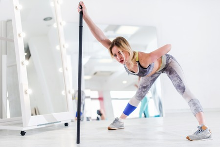 Woman doing stretching exercise for hamstrings and back leaning forward holding barbell in one hand Stock Photo