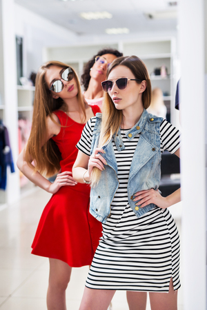 Hot fashionable young women wearing glasses posing looking in mirror standing in womenswear boutique