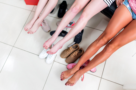 Cropped image of three young women spreading out their long barefoot legs relaxing after choosing shoes in shopping center