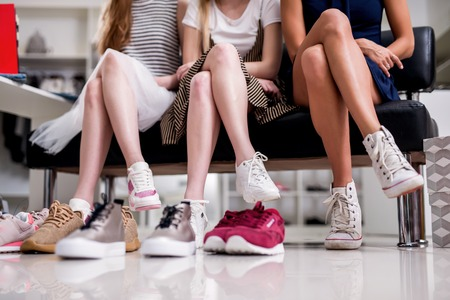 Close-up image of women sitting with legs crossed trying on new sneakers in shopping center Stock Photo