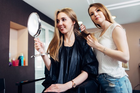 hairdresser: Young female stylist discussing and choosing a new look for a customer sitting on chair looking in makeup mirror in beauty salon