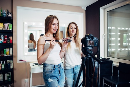 reviews: Two friends doing a makeup products review shooting a video blog standing in front of camera Stock Photo