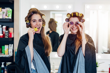 Two funny young girlfriends in hair curlers wearing capes having fun time together in beauty salon. Female friends fooling around with rollers, making faces Stock Photo