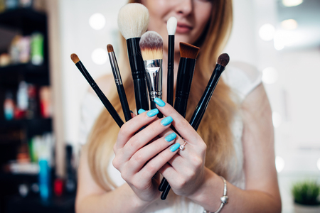 Close-up image of female hands holding a set of make-up brushes Stock Photo