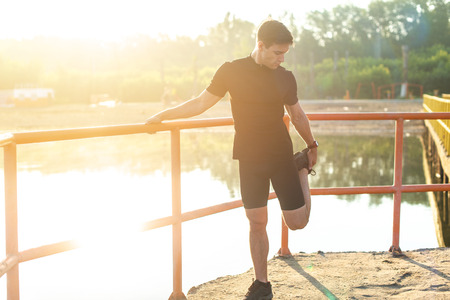 Fitness man stretching his leg before a run outdoors.