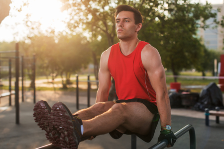 Fit man performing leg raises on outdoor fitness station.
